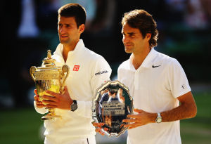 LONDON, ENGLAND - JULY 06:  Novak Djokovic of Serbia poses with the Gentlemen's Singles Trophy next to Roger Federer of Switzerland following his victory in the Gentlemen's Singles Final match on day thirteen of the Wimbledon Lawn Tennis Championships at the All England Lawn Tennis and Croquet Club on July 6, 2014 in London, England.  (Photo by Al Bello/Getty Images)