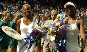 WIMBLEDON, UNITED KINGDOM:  US Serena Williams (L) and her sister Venus hold their trophy's after the Women's final at the Wimbledon Tennis Championships, 06 July 2002. Serena won 7-6 and 6-3. It is the first time in 118 years that sisters have met in the final at Wimbledon.  AFP PHOTO   GERRY PENNY (Photo credit should read GERRY PENNY/AFP/Getty Images)