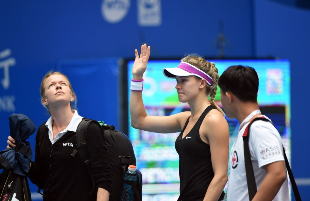 Eugenie Bouchard (C) of Canada waves to the audience after retiring from her first round women's singles match against Andrea Petkovic of Germany at the China Open tennis tournament in Beijing on October 5, 2015.   AFP PHOTO / GOH CHAI HIN        (Photo credit should read GOH CHAI HIN/AFP/Getty Images)