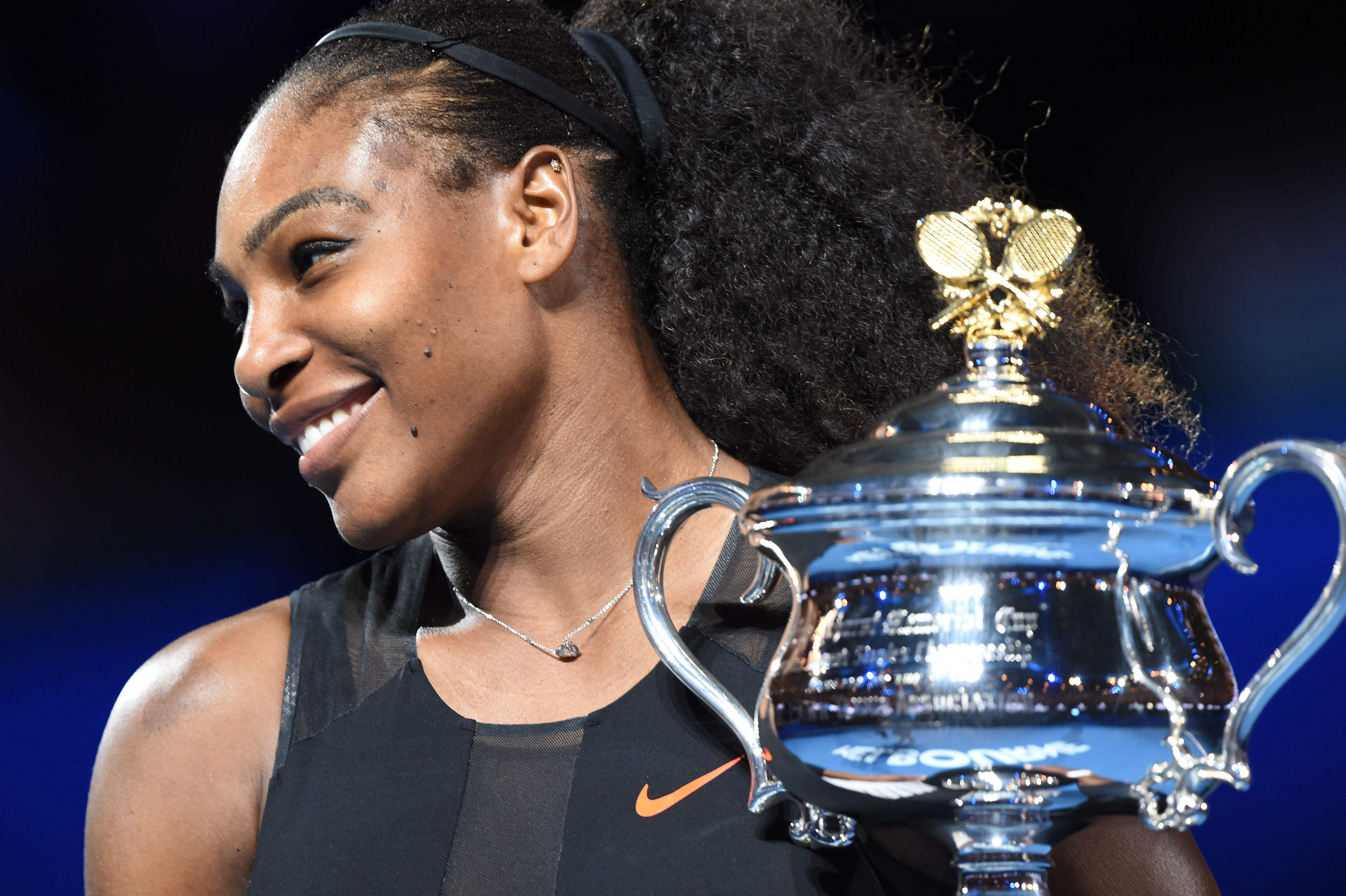 Serena Williams of the US holds up the trophy following her victory over Venus Williams of the US in the women's singles final on day 13 of the Australian Open tennis tournament in Melbourne on January 28, 2017. / AFP / PAUL CROCK / IMAGE RESTRICTED TO EDITORIAL USE - STRICTLY NO COMMERCIAL USE (Photo credit should read PAUL CROCK/AFP/Getty Images)