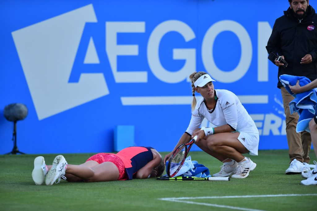 Britain's Johanna Konta (L)lies face down after slipping as Germany's Angelique Kerber looks on during their women's singles quarter-finals tennis match against at the ATP Aegon International tennis tournament in Eastbourne, southern England, on June 29, 2017. Johanna Konta beat Angelique Kerber 6-3, 6-4. / AFP PHOTO / Glyn KIRK (Photo credit should read GLYN KIRK/AFP/Getty Images)